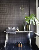 Rustic console table against bathroom wall with anthracite mosaic tiles