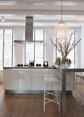 Modern kitchen island with breakfast bar in front of large windows