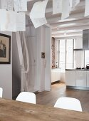 Sheets of paper hanging over dining table in open-plan interior