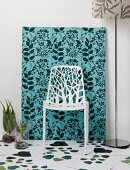 Delicate white chair in front of frame covered in jungle-patterned fabric and leaf pattern on white floor