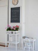 Flowers on plant stand & greeting written on chalkboard in foyer