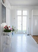 White foyer with front door & flowers on table
