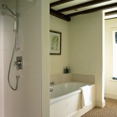 Fitted bathtub and open shower in renovated half-timbered house