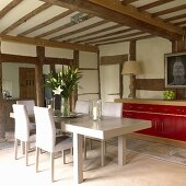 Simple, modern dining area with red sideboard in renovated half-timbered house