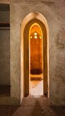 View into bathroom through narrow arched doorway
