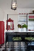 Bar stools with wrought iron and green seat cushions in front of breakfast bar; mirror with red, ornate frame and white, glass-fronted cabinet in background