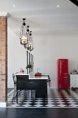 Breakfast bar with integrated hob below vintage, pendant gas lamps; ref fifties fridge in background on black and white floor