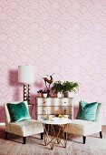 Upholstered chairs and table in front of chest of drawers against pink wallpaper