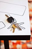Bunch of keys and traced outline on white table
