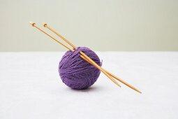 Knitting needles stuck through ball of purple wool