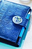 Personal organiser with fastener decorated with button