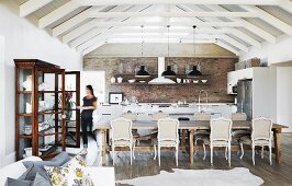Open-plan interior below white roof beams and brick wall in country-house-style kitchen-dining area with antique furniture