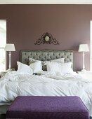Elegant bedroom with upholstered headboard below hand-crafted ornament on wall painted pastel lilac