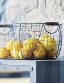 Lemons in vintage wire basket on grey kitchen cabinet