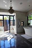 Large bathroom with free-standing bathtub on platform and terrace door