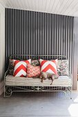 Dog on upholstered metal bench with scatter cushions against metal wall of veranda