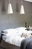 Cone-shaped pendant lamps above simple double bed against grey wall; dog asleep on bed