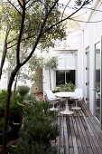 Holzterrasse mit weisser Sitzgruppe und großen Pflanzentöpfen mit mediterranen Pflanzen