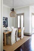 Langer Esstisch mit Hussenstühlen auf hellem Sisalteppich vor großem Hundeportrait