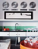 Modern kitchen with green mosaic wall tiles; four clocks showing different times on wall above shelf