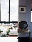 Floor-to-ceiling window with view of cityscape; retro radio and retro TV against wall