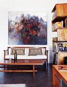 Modern oil painting over elegant wooden sofa; winding bookshelves on wall