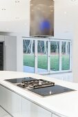 Kitchen counter with gas hob in white worksurface in open-plan modern interior with view through window