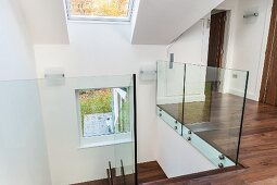 Landing with skylight and glass balustrade in modern, architect-designed house