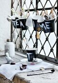 Black paper cups painted with letters and used as containers for teabags, sugar and spoons