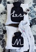 Lettering made from satin ribbon on hot bottles covered with dark fabric