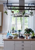 Crockery and food on island counter below stainless steel extractor hood with posies and lit candle lanterns hanging from suspended metal rack