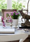 White laptop, pastel flower arrangements and nostalgic stag ornament on desk with framed photo of dog in background