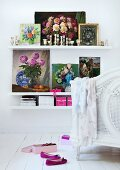 Collection of various pictures of flowers and silver candlesticks on white floating shelves next to foot of white canopied bed on white board floor