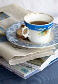 Vintage teacup and biscuits on plate on newspaper