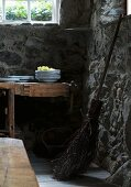 Old besom broom next to stacked plates and grapes on table in cellar room with stone walls