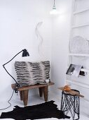 Grey and black scatter cushion on Africa wooden stool and black, animal-skin rug in corner of white room
