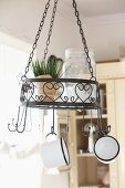 Pot of chives in wrought iron pendant basket with love heart motif and enamel mugs hanging from hooks