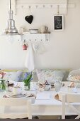 Retro, industrial-style pendant lamp above breakfast table daintily set with white china and blue grape hyacinths; shabby chic ornaments on wall hooks in background