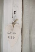 Fabric heart with printed motif tied to old, white-painted door handle with cord