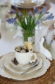 Easter place setting for afternoon tea with bird's nest and bunny biscuit in cup and white china bunny; grape hyacinths in jam jar in background