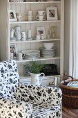 Crockery on country-house shelves behind enamel jug and armchair with black and white floral upholstery