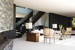 Moderner Wohnraum mit Vintage Sesseln und modernem Sofa vor Treppenaufgang, im Hintergrund schwarz getönte Wand