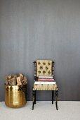 Neo antiker Stuhl mit gepolsterter Sitz- und Rückenfläche, Bücherstapel auf Sitzfläche, daneben Messingbehälter mit Holzscheiten vor grauer Wand