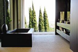 Schwarze Badewanne gegenüber eingebautem Waschtisch, im Hintergrund Fensterfront mit Blick auf Baumgruppe