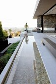 Long, narrow pool adjoining terrace of contemporary house with panoramic view of city