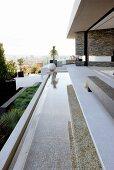 Langes, schmales Wasserbecken vor Terrasse eines zeitgenössischen Wohnhauses mit Panoramablick auf Stadt