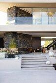 Terrasse mit Outdoormöbeln und weissen Deko Kugeln auf Stufen, darüber Obergeschoss des zeitgenössischen Wohnhauses mit Glasbrüstung vor Terrasse