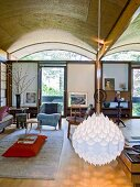 White, droplet-shaped pendant lamp in comfortable living room with eclectic furnishings and barrel-vaulted ceiling
