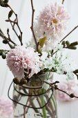 Einmachglas mit Bügelverschluss gefüllt mit Hyazinthen, Lenzrosen, Erlenzweigen und Allium