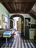 Foyer with black and white chequered floor and stacked books on console table below wooden gallery in country house